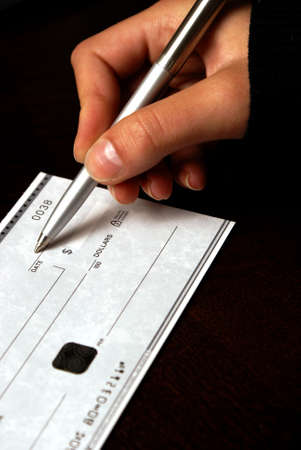 A macro shot of a person writing a cheque.