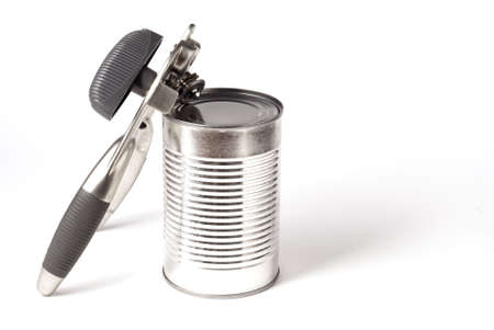 unopen: An isolated tin can with a can opening tool leaning up on it. Stock Photo