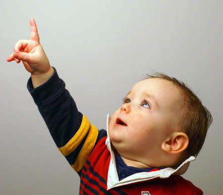 A baby shows interest at something by pointing his finger in the air. Stock Photo