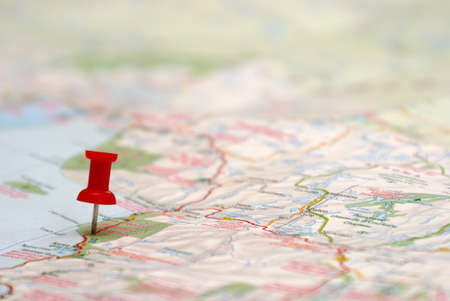 red pushpin: A push pin is inserted on a travel destination of a map.