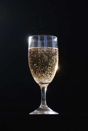 A glass of champagne with bubbles exceeding the rim.