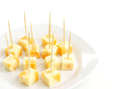 toothpick: A plate of cheese cubes with toothpicks.