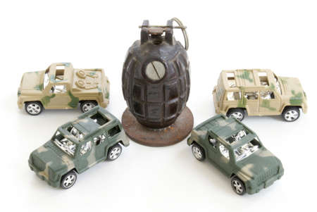 Four toy military vehicles surround a hand grenade.