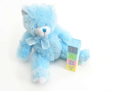 A blue teddy bear sits next to the word baby. photo