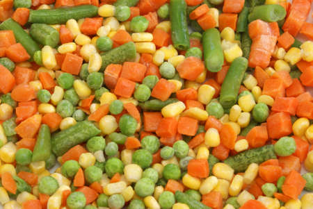 A macro of frozen peas, carrots, corn, and green beans.