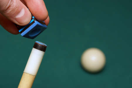 Someone is chalking his cue-stick before he shoots the ball. Archivio Fotografico