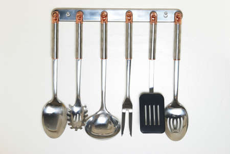 A rack of kitchen utensils hanging on the wall. Stok Fotoğraf
