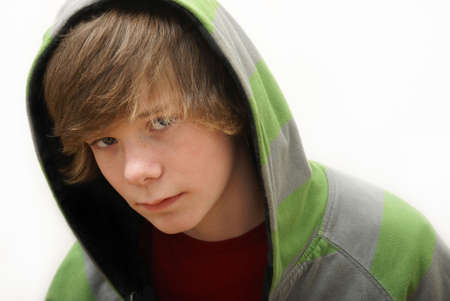 hooded: A young teenage boy wearing a green and gray hoodie. Stock Photo