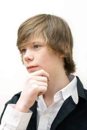 A teenage boy sits and thinks deeply.