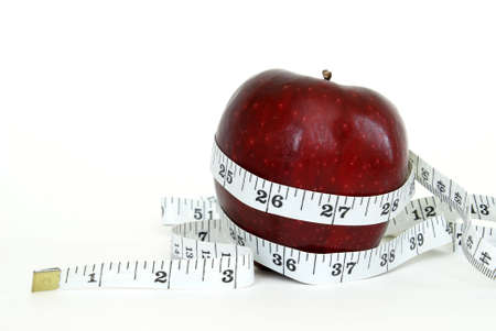 A red apple with a measuring tape wrapped around it for the concept of healthy eating. Stock Photo