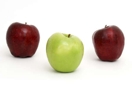 A green apple leads the other two red ones.