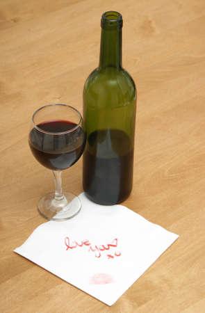 bebes niñas: Una mujer escribe una nota de amor en una servilleta, al lado de una botella de vino. Foto de archivo