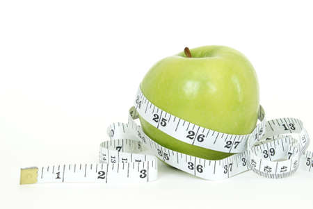 A green apple with a measuring tape wrapped around it for the concept of dieting.