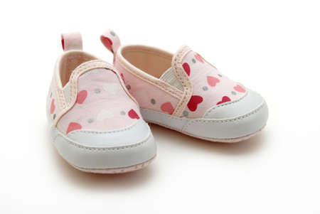 kid feet: A pair of baby girls shoes on white background.