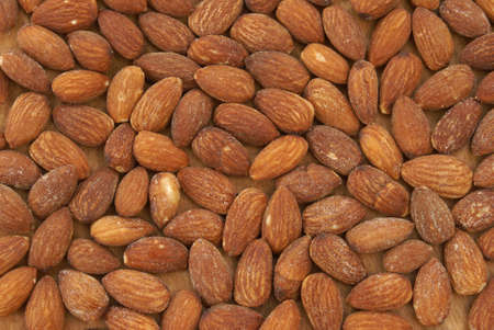 A macro of many almonds on a piece of wood. photo