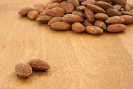 heaping: A heaping pile of almonds behind two that are away from the rest. Stock Photo