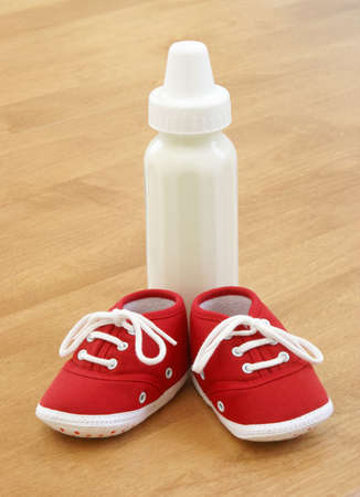 nursing bottle: A bottle and a pair of shoes are sitting on a table.