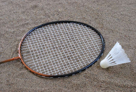 passtime: Badminton equipment lying on the sand at the beach. Stock Photo