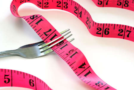 A dieting concept with a fork and a measuring tape. photo