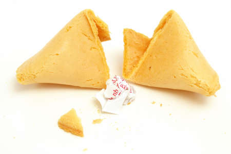 A fortune cookie cracked open with the message crumpled into a ball. photo