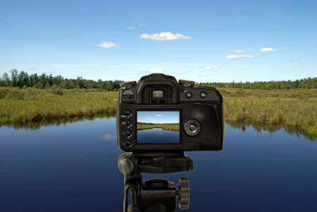 viewfinder: A digital camera is taking a picture of a beautiful landscape. Stock Photo