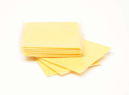 A stack of processed cheese slices over white background.