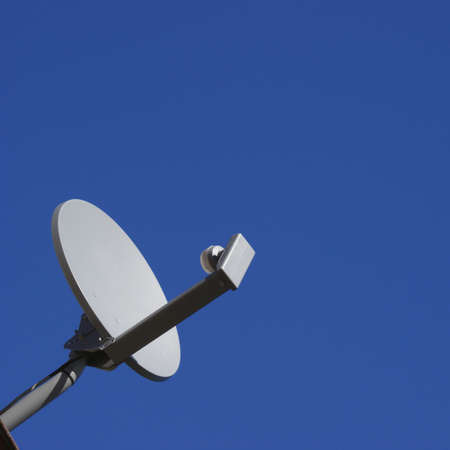 dish disk: A satellite dish over a bright blue sky.