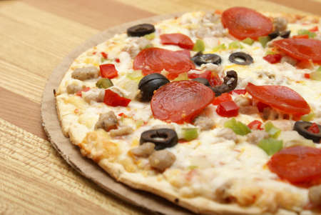 A fresh thin crust pizza sitting on the counter. photo