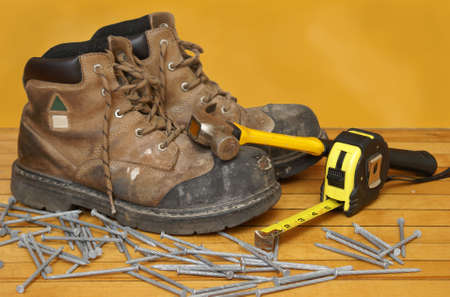 steel toe boots: A pair of construction grade work boots with some other tools.