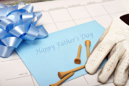 A card for father lays on a calendar with other accesories for the celebration. photo