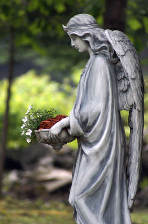 angel statue: A statue of an angel holding a bed of flowers.
