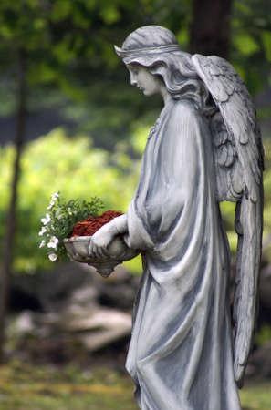 Une statue d'un ange tenant un lit de fleurs.