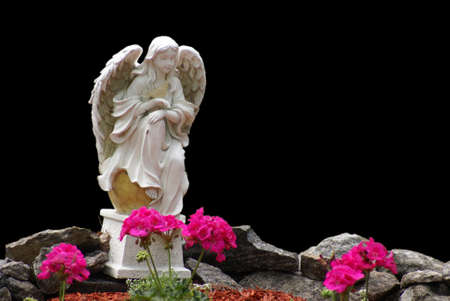 A statue of an angel before a bed of flowers.