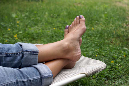 A woman relaxes in her lawn chair and kicks up her feet. Reklamní fotografie