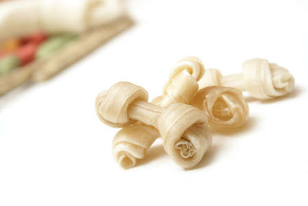rawhide: A pile of small rawhide bones infront of a bunch of other treats.