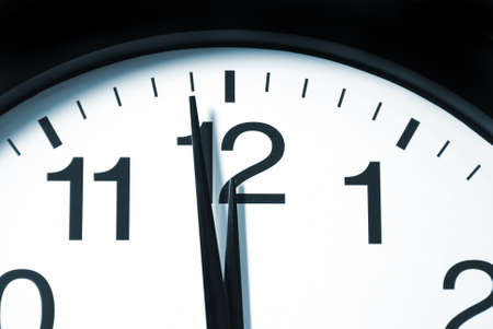 A macro shot of a clock with one minute left to 12. Stock Photo