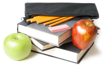 A stack of school books with an open pencil case and some apples. photo