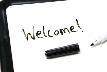 The word welcome is hand written in marker on an office white board. photo