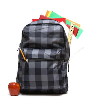utiles escolares: Una mochila llena de escuela suministra lista para los regreso a clase de los estudiantes.