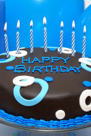 A birthday cake waits with its lit candles for that special somebody to make his wish. Stock Photo - 7565726