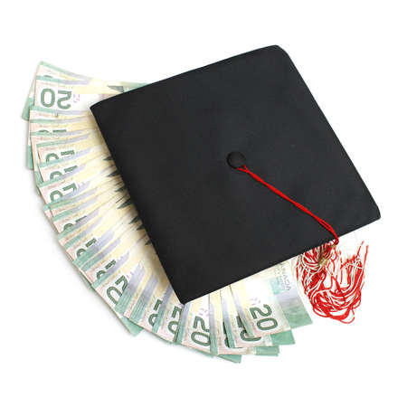 fee: A grad hat with spread out money for an education or tuition fee concept.