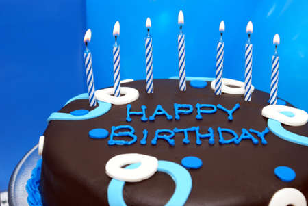 A birthday cake waits with its lit candles for that special somebody to make his wish. photo