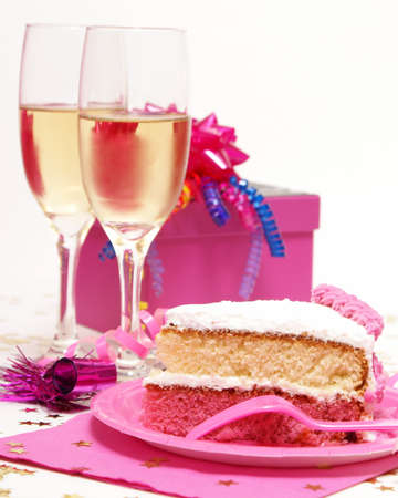 A slice of cake in front of two glasses of champagne.