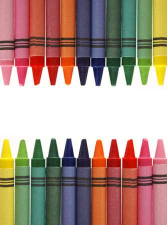 Een centraal frame gemaakt van verschillende gekleurde waskrijtjes, waardoor er ruimte is voor uw tekst. Stockfoto