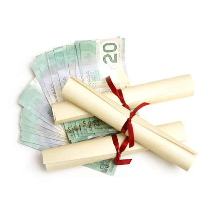 alumna: A few diplomas with spread out money for an education or tuition fee concept.