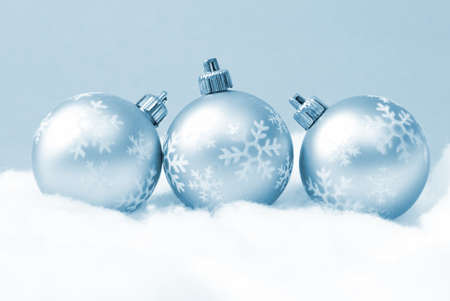 Three holiday baubles on some fake snow and coloured in blue monochrome.