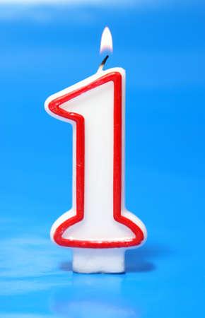 numero uno: Una sola vela encendida en la forma de un número uno está rodeada de una atmósfera azul calmante.