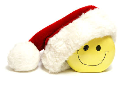 An isolated shot of a smiley face wearing a santa hat for the holiday season.
