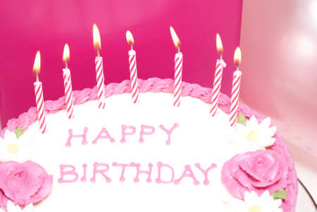 A girls birthday cake with some lit candles.
