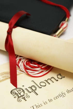 business degree: A diploma and grad hat represent a high achieving student.